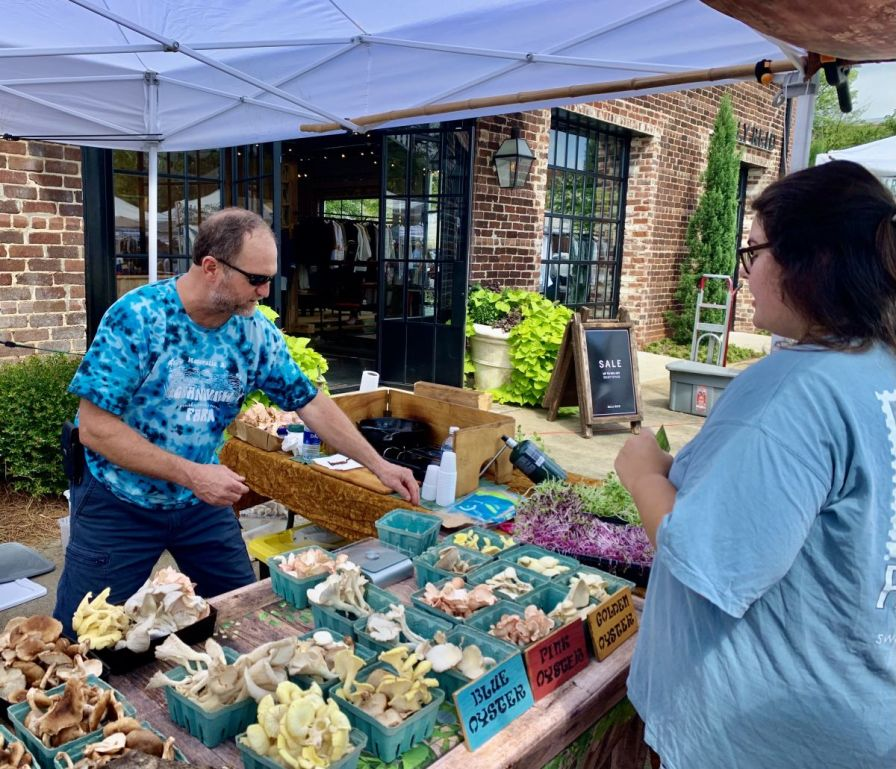 Crowther bags mushrooms for a customer. (Donna Cope / Alabama NewsCenter)
