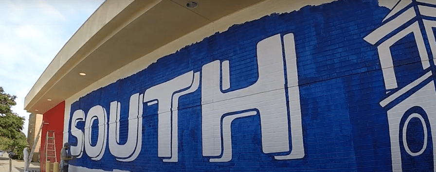 Andy Scott of New Hand Signs works on a 69-foot-by-12-foot mural on a wall of the University of South Alabama Student Center. The work took about a week to complete. (screen grab)