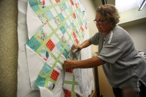 Kimmie Monteabaro places a row of blocks on a design wall so she can see how her quilt top will look when completed. (Meg McKinney / Alabama NewsCenter)