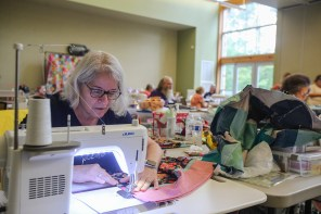 Susan Wagner sews a pillowcase during her presentation, to show how quickly one can be made, to coordinate with a quilt and for storing quilts. (Meg McKinney / Alabama NewsCenter)