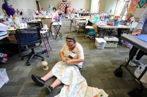 Sometimes it's easier to sit on the floor to assemble rows of quilt blocks, as Kimmie Monteabaro pins blocks together. The conference room was turned into a large sewing room filled with machines, fabrics, supplies, tools and quilters. (Meg McKinney / Alabama NewsCenter)