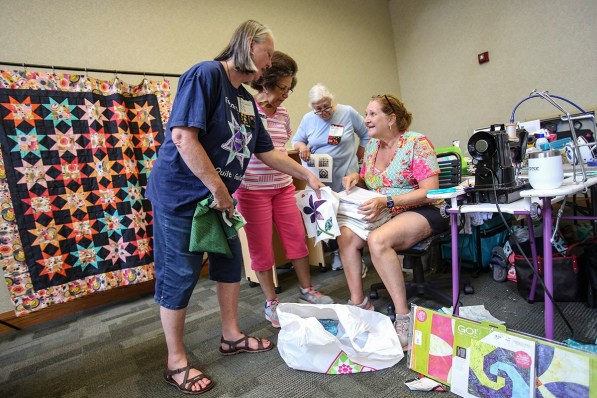 Shopping for fabrics is a pastime for quilters. Vicki Moore, seated, shows her latest purchases to Melonie Graham, left, and Ella Thomas, center; following a trip to a local quilt shop. (Meg McKinney / Alabama NewsCenter)