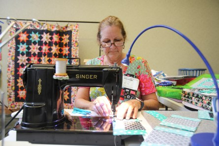 Vintage sewing machines are popular among quilters because of their ease of use and straight stitch quality. Vicki Moore sews blocks on a Singer 301 machine, surrounded by contemporary notions and accessories. (Meg McKinney / Alabama NewsCenter)