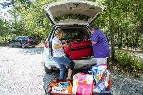 Packing and loading sewing machines, fabrics and supplies for a retreat often requires teamwork. Peggy Plyler, left, and Hilda Childress, right, lift a sewing machine case into Childress' SUV at the end of the retreat. (Meg McKinney / Alabama NewsCenter)