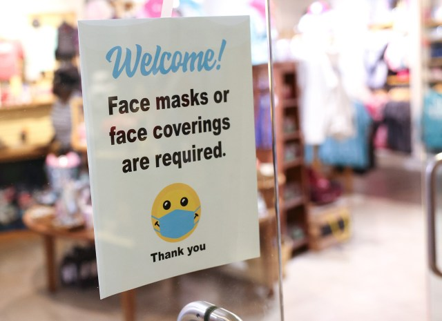 A sign requiring mask use is seen outside of a store in Union Station on July 30