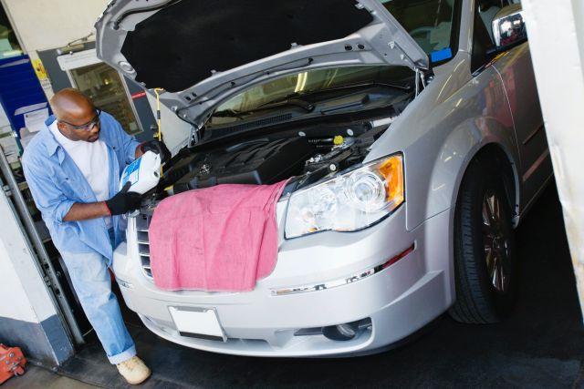 Mechanic works on car under the hood