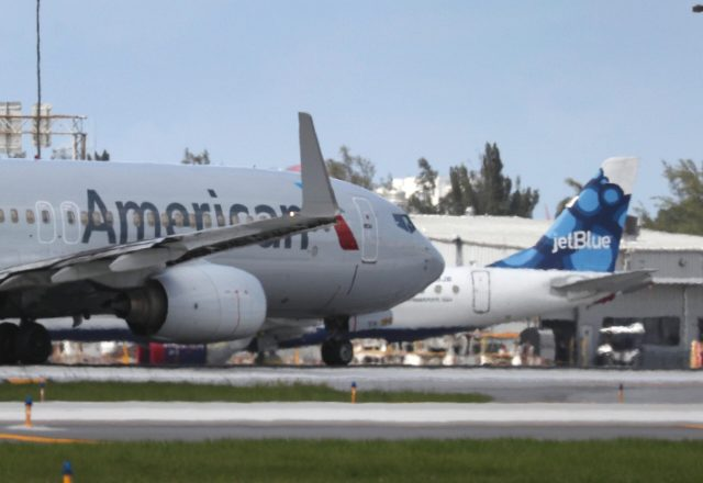 An American Airlines plane takes off near a parked JetBlue plane at the Fort Lauderdale-Hollywood International Airport on July 16
