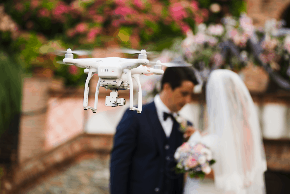 A drone hovers snapping pictures of a couple during their wedding vows