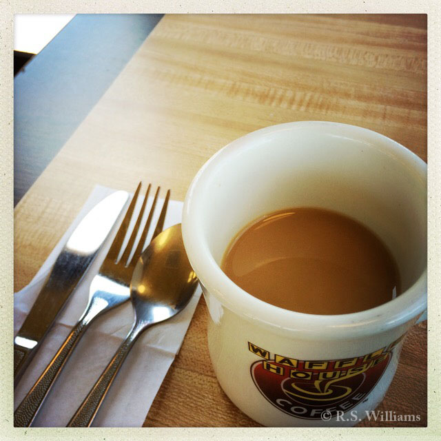 In foreground: a Waffle House logo coffee cup about half-full of light coffee, and to its left are three a knife, fork, and spoon on a white paper napkin. The rest of the frame is a wood-grain (Formica) laminate table top, light in the middle and dark around the table edges.