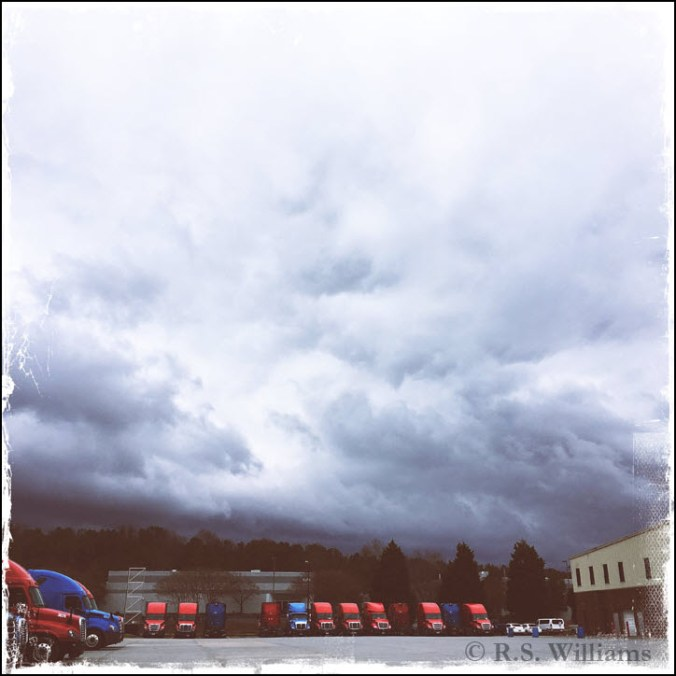 A sky filled with roiling dark gray clouds looms above a large parking area for a trucking company. In the background and at the left foreground, the dozen or so 18 wheelers (each of which is 13 feet high) and the truck garage (which stands about 30 feet high) resemble children's toys about to be swept away by the massive, looming storm behind them.