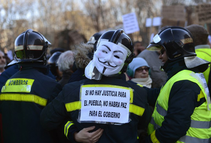 """A firefighter wearing a Guy Fawkes mask and holding a placard reading """"If there is no justice for the people, there will be no peace for the government"""" attends a demonstration on February 23, 2013 in Madrid. (AFP Photo / Pierre-Pholippe Marcou)"""