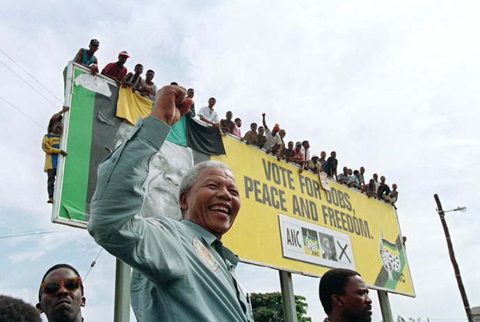 African National Congress (ANC) President Nelson Mandela greets young supporters who wait for atop a billboard in a township outside Durban, 16 April 1994 prior to an election rally. (AFP Photo / Alexander Joe)