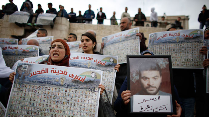 """Palestinians hold posters with pictures of Palestinian prisoners during a protest marking """"Palestinian Prisoners Day"""" at Damascus Gate in Jerusalem's Old City April 17, 2013.(Reuters / Ammar Awad)"""