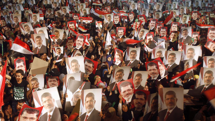 Members of the Muslim Brotherhood and supporters of Egypt's President Mohamed Mursi hold pictures of him as they react after the Egyptian army's statement was read out on state TV, at the Raba El-Adwyia mosque square in Cairo July 3, 2013.(Reuters / Khaled Abdullah)
