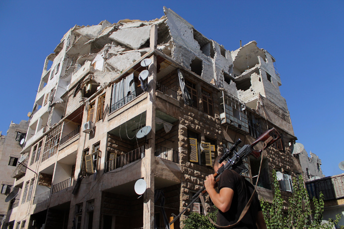 A Free Syrian Army fighter walks with his weapon in front of a damaged building in Aleppo's Al-Ezaa neighbourhood, September 1, 2013 (Reuters / Malek Alshemali)