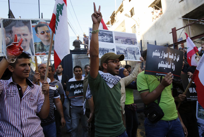 Lebanese supporters of Syrian President Bashar al-Assad (portrait-L) flash the sign for victory as they wave their national flag, during a demonstration near the American embassy, east of Beirut against a possible US military strike on Syria on September 6, 2013. (AFP Photo)
