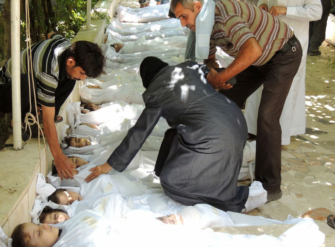 A woman mourning over a body wrapped in shrouds laid out in a line on the ground with other victims which Syrian rebels claim were killed in a toxic gas attack by pro-government forces in eastern Ghouta, on the outskirts of Damascus on August 21, 2013.(AFP Photo / Shaam News Network )