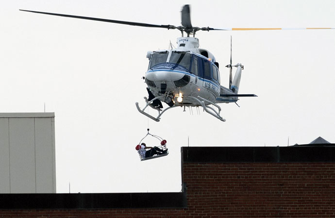 A helicopter lifts a person off the roof as police respond to the report of a shooting at the Navy Yard in Washington, Dc on September 16, 2013.(AFP Photo / Saul Loeb)