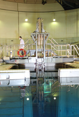 Metal-encased rod with 20 percent enriched nuclear fuel as it is inserted into Tehran's reactor (AFP Photo)