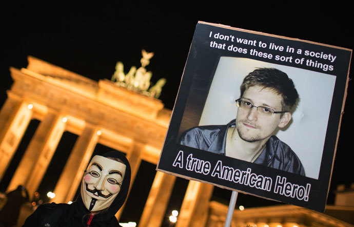 "A supporter of the Anonymous group wearing a Guy Fawkes mask holds up a placard featuring a photo of US intelligence leaker Edward Snowden and reads ""A true American Hero!"" during a rally in front of Berlin's landmark Brandenburg Gate on November 5, 2013.(AFP Photo / Florian Scuhu)"
