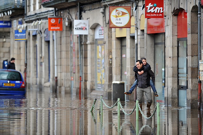 A man carries a boy in a flooded street in Morlaix, Britanny, where the city center is under 1.4 metres (four feet) of water on December 24, 2013. (AFP Photo / Frank Perry)