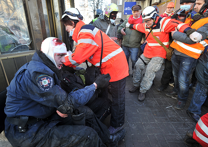 Red Cross workers give first aid to policemen wounded during clashes with anti-government rioters in Kiev on February 18, 2014. (AFP Photo / Genya Savilov)