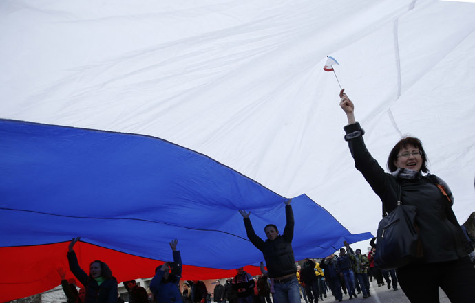 People march on the street with a giant Russian flag in Simferopol, Crimea March 1, 2014. (Reuters/David Mdzinarishvili)