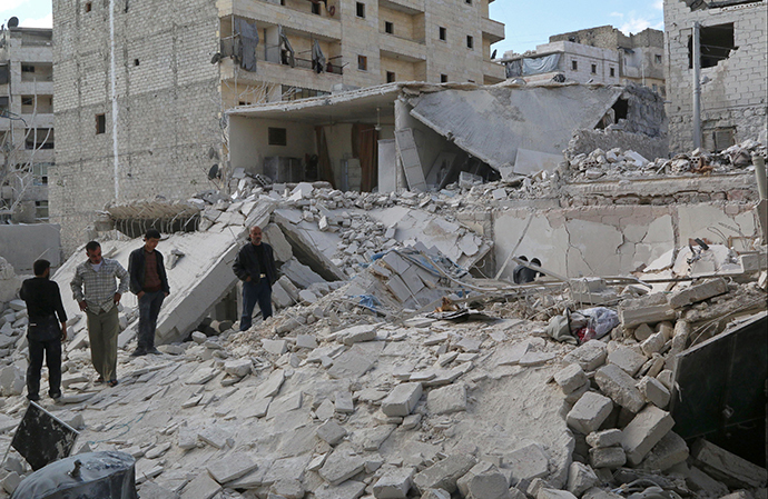 Civilians inspect a site hit by what activists said were barrel bombs dropped by forces loyal to Syria's President Bashar al-Assad in Karam Homad district in Aleppo March 26, 2014. (Reuters / Mahmoud Hebbo)