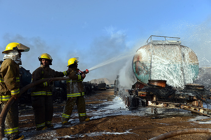 Afghan firefighters attempt to extinguish burning fuel trucks following an overnight attack by Taliban militants in Chawk-e-Arghandi on outskirts of Kabul on July 5, 2014. (AFP Photo / Wakil Kohsar)