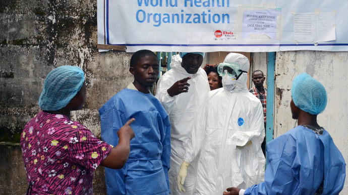 Health workers in protective gear pose at the entrance of the Ebola treatment unit of the John F. Kennedy Medical Center, in the Liberian capital Monrovia, on October 13, 2014.(AFP Photo / Zoom Dosso)