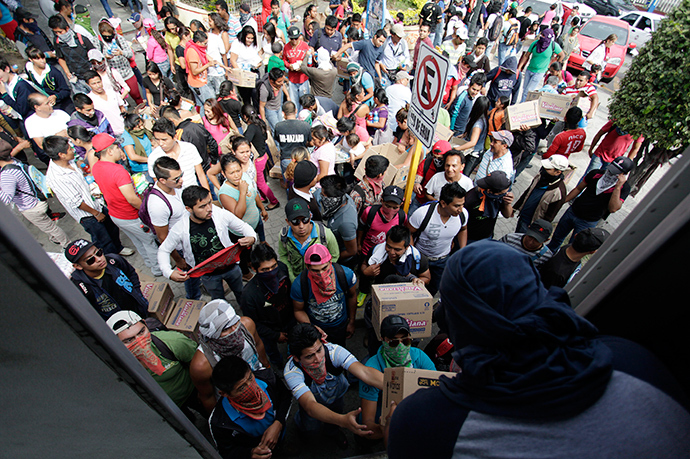 Student teachers hand out merchandise from a truck, which they blocked on a highway, during a protest in support of 43 missing students, in Chilpancingo, November 7, 2014 (Reuters / Daniel Becerril)