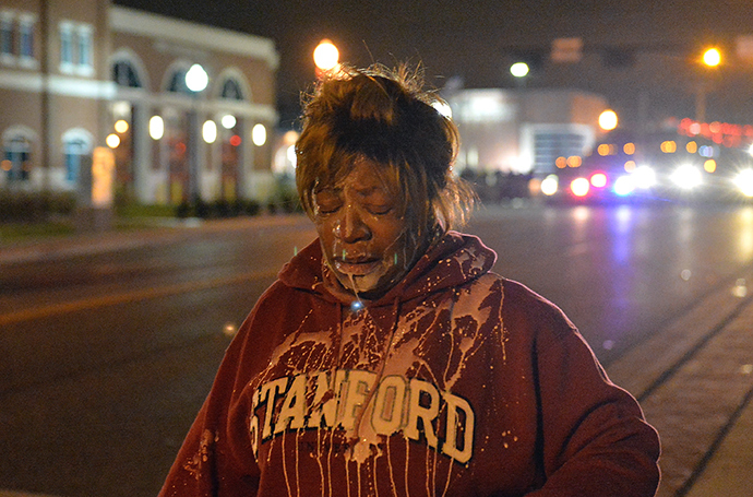 A protestor retreats after being treated for tear gas as demonstrators protest the death of 18-year-old unarmed black teenager Michael Brown, who was shot to death by a white police officer, in Ferguson on November 24, 2014 (AFP Photo)