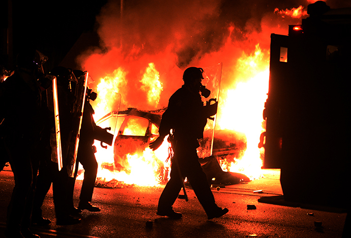 Police chase protesters passing by one of their burning cars during clashes following the grand jury decision in the death of 18-year-old Michael Brown in Ferguson, Missouri, on November 24, 2014 (Reuters / Jewel Samad)