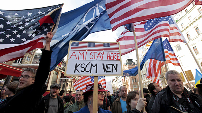 "Supporters of the U.S. Army's ""Dragoon Ride"" military exercise wave U.S. flags as they oppose a demonstration against the exercise in Prague March 28, 2015 (Reuters / David W Cerny)"