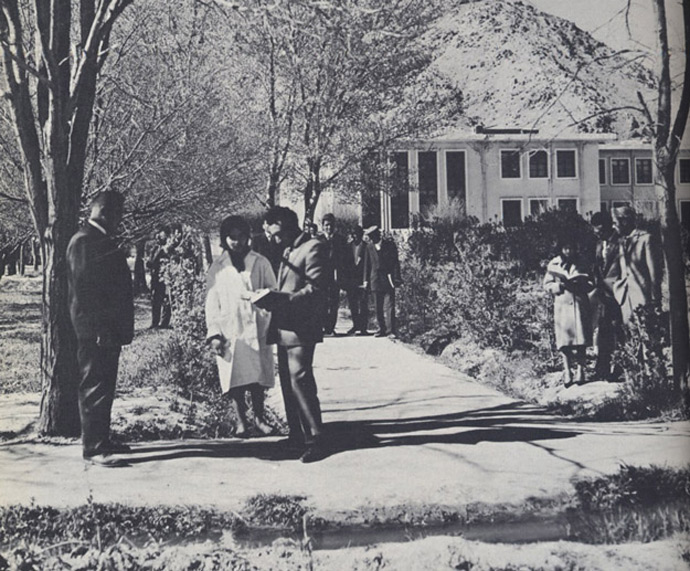 "Original caption: ""Kabul University students changing classes. Enrollment has doubled in last four years."" The physical campus of Kabul University, pictured here, does not look very different today. But the people do. In the 1950s and '60s, students wore Western-style clothing; young men and women interacted relatively freely. Today, women cover their heads and much of their bodies, even in Kabul. A half-century later, men and women inhabit much more separate worlds."
