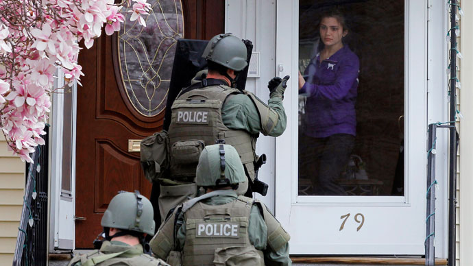 A member of the SWAT team motions to a resident to come out of the house as they conduct a house to house search for Dzhokar Tsarnaev, the one remaining suspect in the Boston Marathon bombing, in Watertown, Massachusetts April 19, 2013.(Reuters / Brian Snyder)