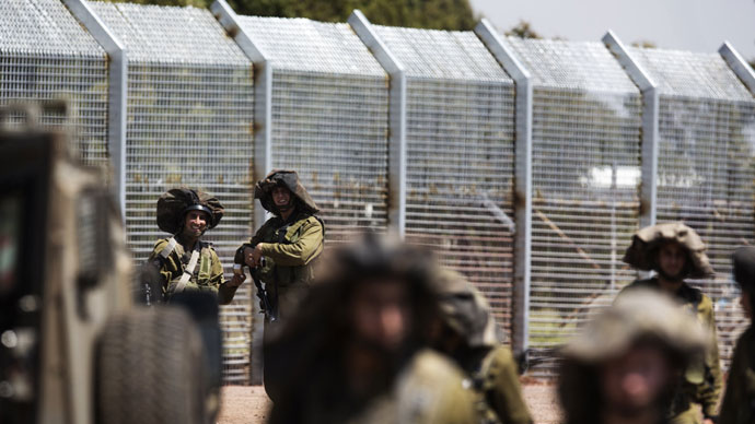 Israeli soldiers stand guard as Syrian residents (unseen) approach the Syria-Israel border in the Israeli annexed Golan Heights, near the southern Syrian village of Ar Rafide, on May 7, 2013.(AFP Photo / Menahem Kahana)