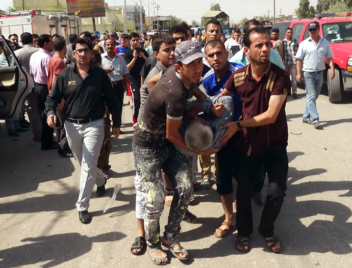 A wounded man is carried away following a suicide bombing close to the home of MP Imad Yohana in the northern city of Kirkuk on September 22, 2013, in which some 47 people were wounded including the Christian MP. (AFP Photo / Marwan Ibrahim)