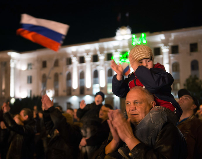 A young boy sitting on the shoulders of an elderly man claps as people watch fire works in the center of the Crimean city of Simferopol on March 21, 2014. (AFP Photo)