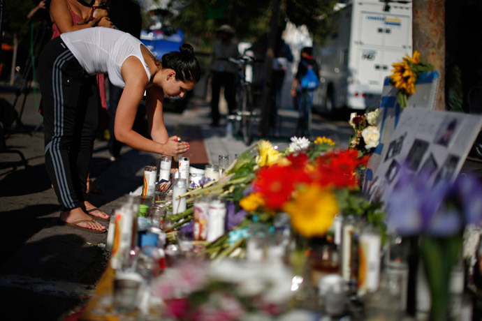 A woman lights a candle at a makeshift memorial for 20-year-old UCSB student Christopher Michael-Martinez outside a deli that was one of nine crime scenes after series of drive-by shootings that left 7 people dead in the Isla Vista neighborhood of Santa Barbara, California May 25, 2014. (Reuters / Lucy Nicholson)