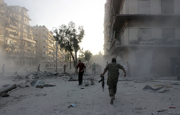 Syrians run for cover during an airstrike on the Bustan al-Qasr rebel held neighbourhood of the northern Syrian city of Aleppo on May 30, 2014 (AFP Photo / Karam Al-Masri)