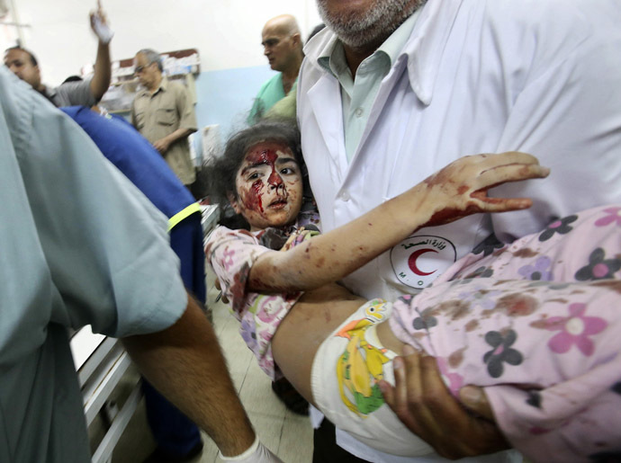 A Palestinian medic carries a girl, who medics said was wounded by Israeli shelling, at a hospital in Khan Younis in the southern Gaza Strip July 23, 2014. (Reuters)