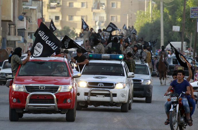 Militant Islamist fighters waving flags, travel in vehicles as they take part in a military parade along the streets of Syria's northern Raqqa province, June 30, 2014 (Reuters)
