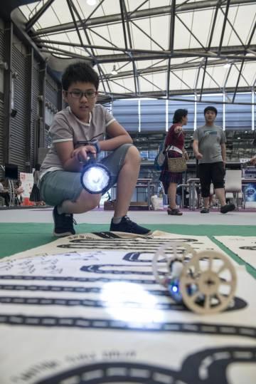Un niño guía su robot con ruedas, programado para que siga la luz de una linterna.