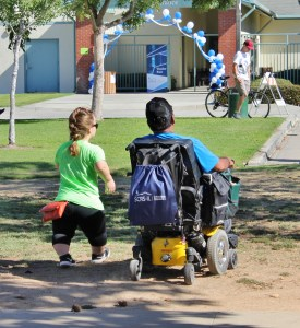 Two people are moving towards a balloon arch in the distance. One is in a wheelchair, the other is a little person.