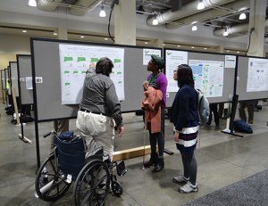 Three people discuss a poster in the poster hall at a conference