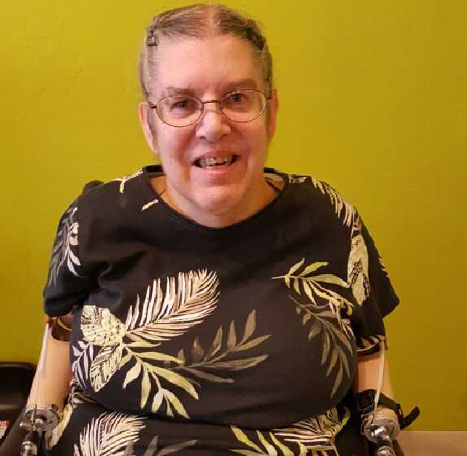 Sue Lockaby-Eakin an older woman with prosthetic arms using a wheelchair in a brown shirt with glasses