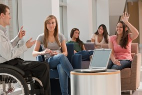 Teacher with spinal cord injury giving a lecture to students in classroom