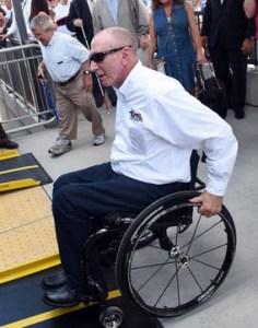 a man using a wheelchair gets onto a bus.