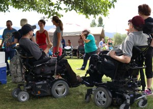 A group of people in a community park enjoying a picnic. Two of the people are using powerchairs.